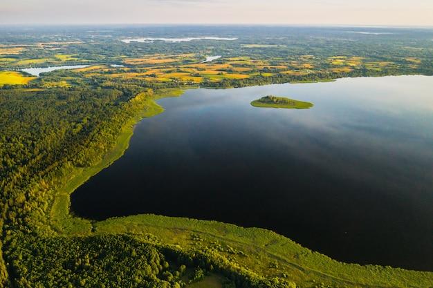 Lac drivyaty dans la forêt dans le parc national des lacs braslav au coucher du soleil