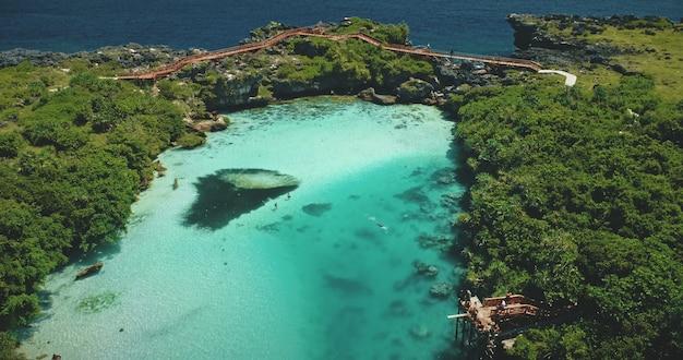 Lac d'eau salée au paysage tropical vert avec des plantes, des arbres, de l'herbe de la lagune de weekuri, l'île de sumba en indonésie, en asie. vacances d'été majestueuses au loch d'eau salée sur la falaise au bord de l'océan