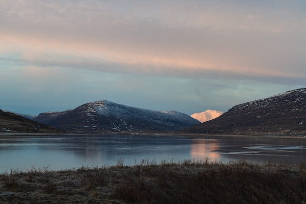 Lac entouré de collines couvertes de neige se reflétant sur l'eau pendant le coucher du soleil en islande