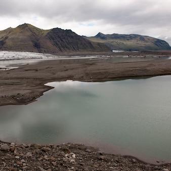 Lac glaciaire et plaine, montagnes