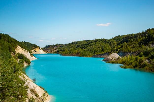 Lac insolite aux eaux turquoises dans le cratère. carrière de craie de la côte rocheuse rocheuse en biélorussie. journée d'été ensoleillée.