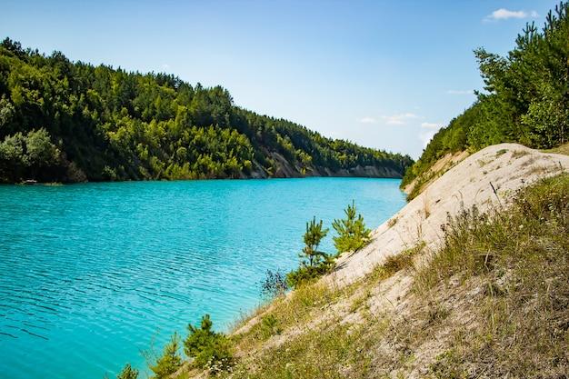 Lac insolite aux eaux turquoises dans le cratère. carrière de craie de rivage pierreux rocheux en biélorussie. journée d'été ensoleillée.