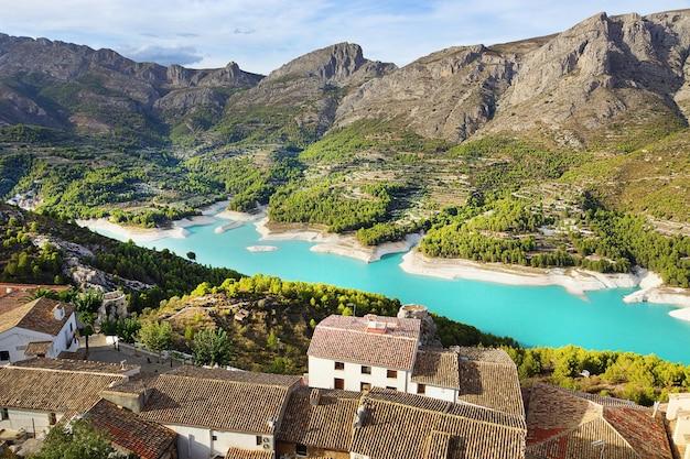 Un lac magnifique en espagne avec une eau bleue douce caché entre des montagnes avec de petites villes