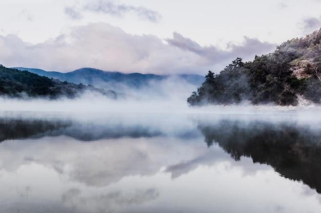 Lac de montagne au petit matin. le soleil n'est pas encore levé. fumée au-dessus de l'eau. au loin les montagnes bleues