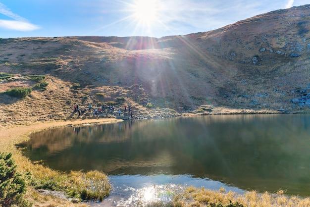 Lac des montagnes avec reflet dans l'eau bleue, lumière du matin et soleil brillant