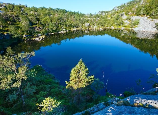 Lac de norvège de petite montagne bleu profond avec rivage rocheux