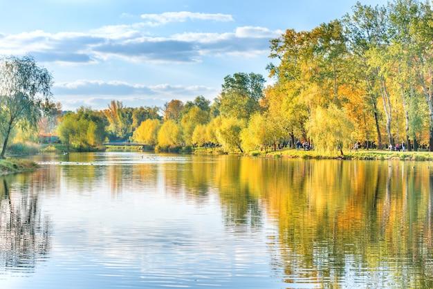 Lac avec des oiseaux dans le parc de la ville d'automne avec des marcheurs
