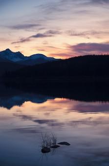 Lac patricia avec chaîne de montagnes et réflexion de la forêt de pins le soir
