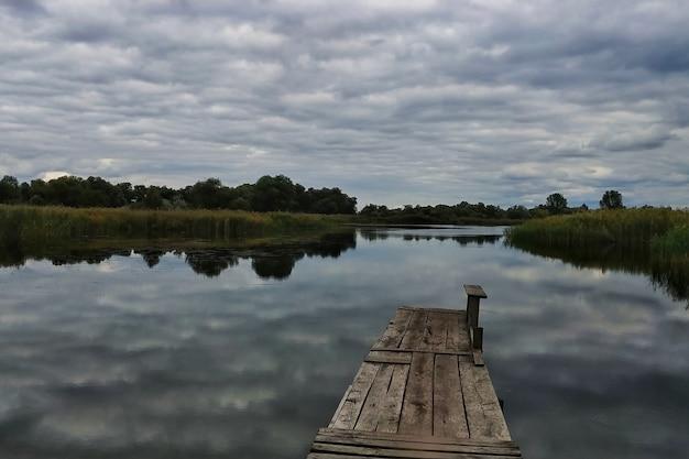 Un lac avec un pont en bois, de beaux nuages dans le ciel.