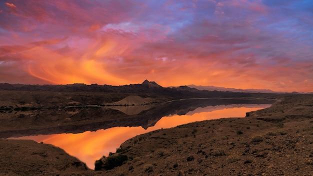 Lac sur prairie au coucher du soleil