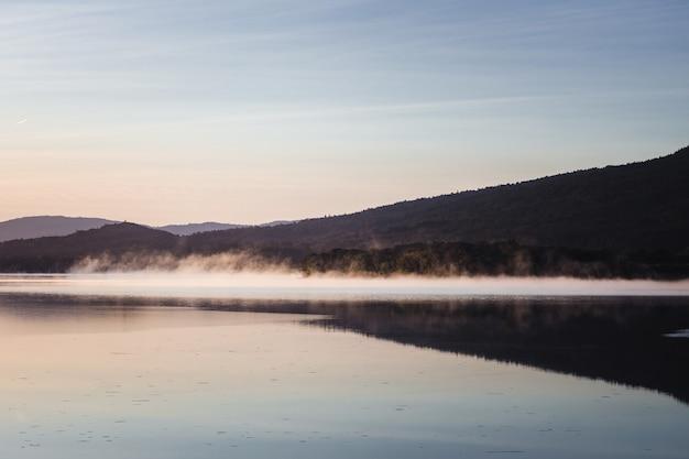 Lac près de la montagne sous un ciel bleu pendant la journée