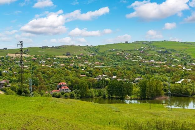 Lac près d'un village aux collines verdoyantes