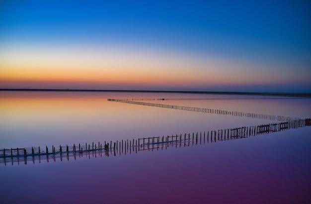 Lac rose salé brillant et un chemin le long