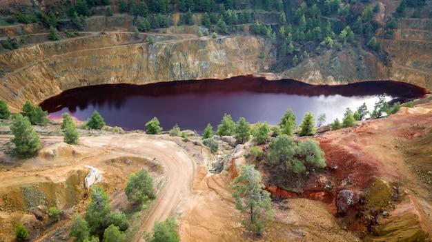 Lac rouge mitsero (chypre). les produits chimiques toxiques de la mine à ciel ouvert de sulfure de kokkinopezoula lui ont donné une teinte rouge et jaune artificielle.
