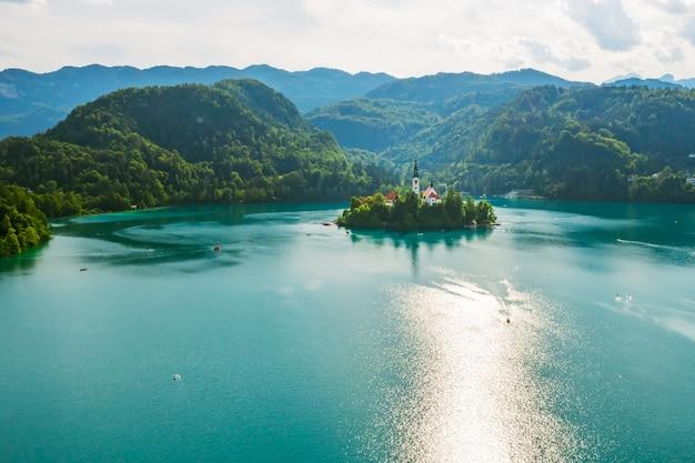 Lac saigné avec de l'eau bleu turquoise avec une petite île sur fond d'alpes juliennes