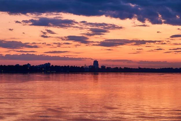 Lac et ville avec coucher de soleil coloré