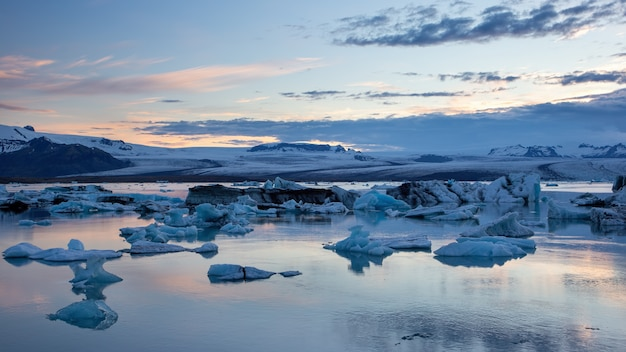 Lagon glaciaire à l'aube avec de la glace flottant dans l'eau