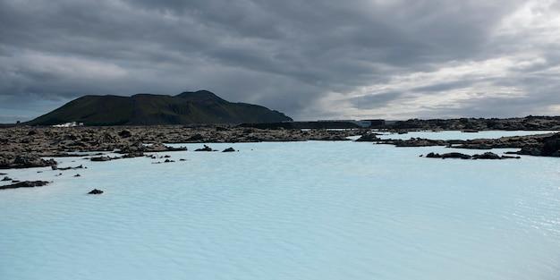 Lagune géothermique volcanique, paysage accidenté, ciel orageux