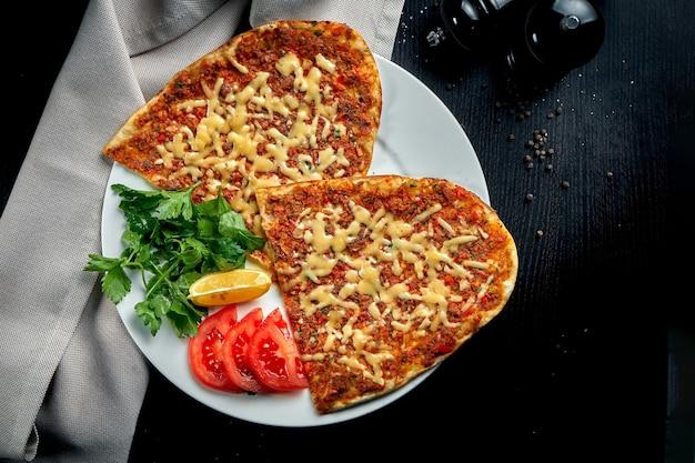 Lahmacun est un plat turc populaire. tortilla fine croustillante avec agneau haché, tomates et poivron sur fond noir