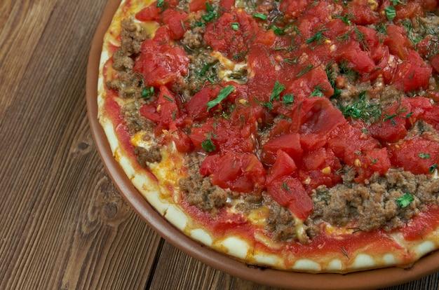 Lahmacun - morceau de pâte rond et fin garni de viande hachée et de légumes hachés