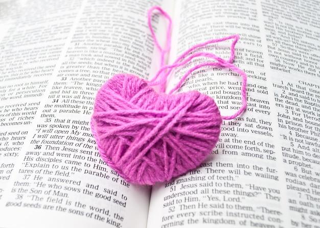 Laine à tricoter coeur rose mis sur le livre, saint valentin