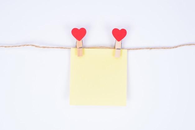 Laissant le concept de félicitations secrètes. la photo en gros plan de petit autocollant papier jaune accroché sur une corde attachée avec des pinces à linge en forme de coeur isolé sur fond blanc
