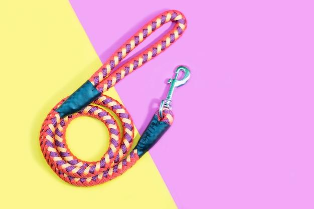 Laisse de chien sur fond rose et jaune. concept d'accessoires pour animaux de compagnie.