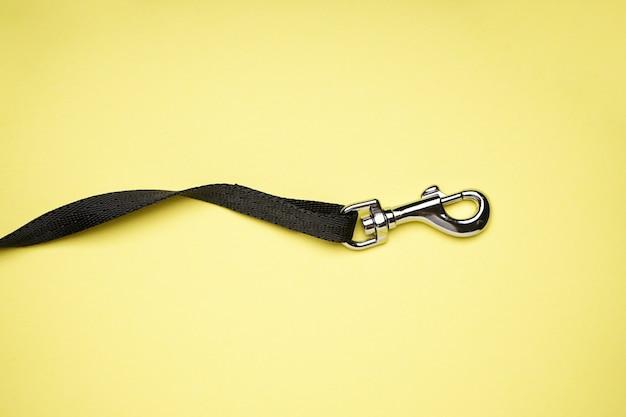 Laisse de chien avec mousqueton sur fond jaune, mise à plat.