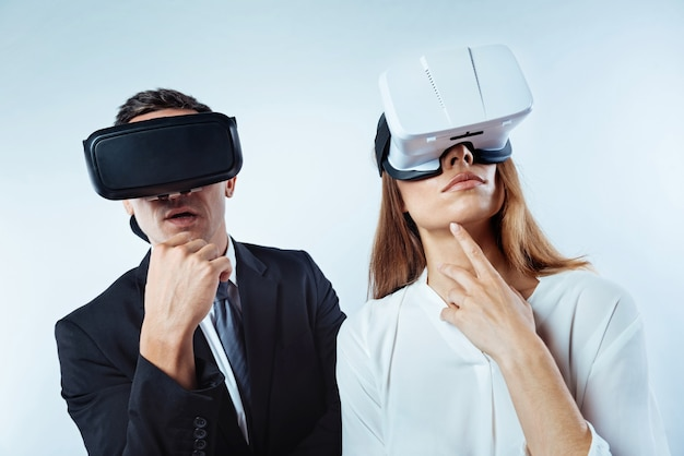 Laisse-moi penser. des collègues attentionnés se tenant côte à côte et rêvant tout en portant des casques de réalité visuelle 3d en arrière-plan.