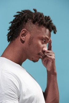 Laisse-moi penser. homme afro-américain songeur douteux avec une expression réfléchie faisant le choix sur fond bleu