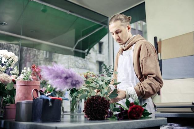 Laisse-moi penser. homme blond attentif à l'aide de fleurs lors de la composition du bouquet