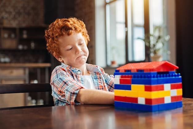 Laisse-moi penser. mise au point sélective sur un petit enfant pensif qui regarde attentivement une maison construite et y pense après avoir joué avec un ensemble de construction.