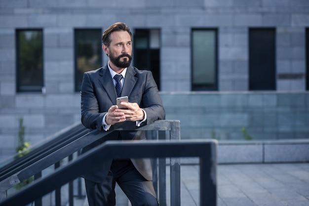 Laisse-moi penser. professiaonl homme d'affaires confiant tenant un téléphone tout en s'appuyant sur une main courante