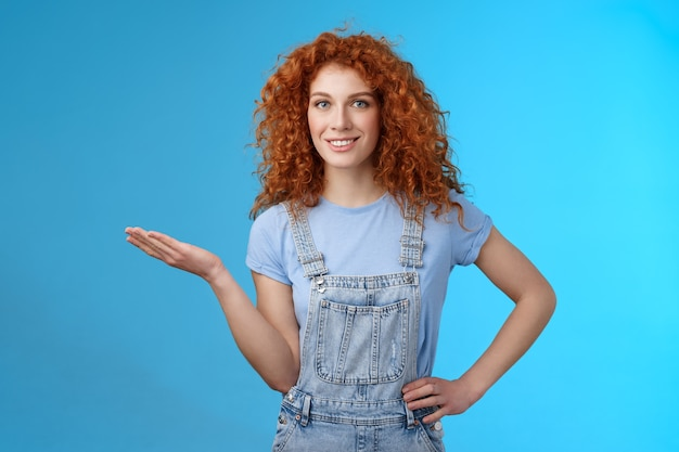 Laissez-moi vous montrer un produit cool. modèle féminin roux confiant et gai attrayant coiffure frisée présente l'objet des clients tenir l'espace de copie bleu vierge de la paume de la publicité debout sur fond bleu.