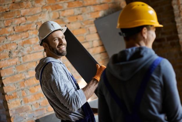 Laissez-nous vous aider. joyeux jeunes constructeurs masculins portant des casques souriants, tenant un goujon métallique pour les cloisons sèches tout en travaillant ensemble sur le chantier de construction