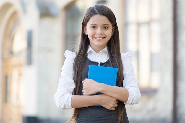 Laissez parler le livre. un enfant heureux tient un livre de bibliothèque. bibliothèque de l'école. lecteur de bibliothèque à l'extérieur. rat de bibliothèque mignon retour à l'école. l'éducation formelle. journée du savoir. bibliopole. librairie. 1er septembre.