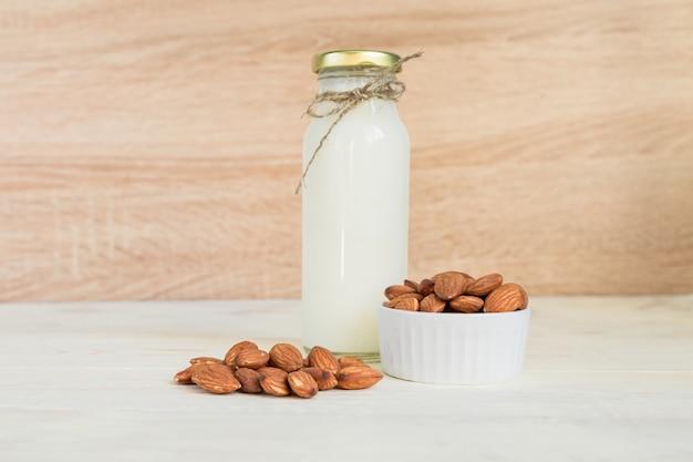Lait d'amande fait maison dans une bouteille et noix dans un bol en porcelaine blanche