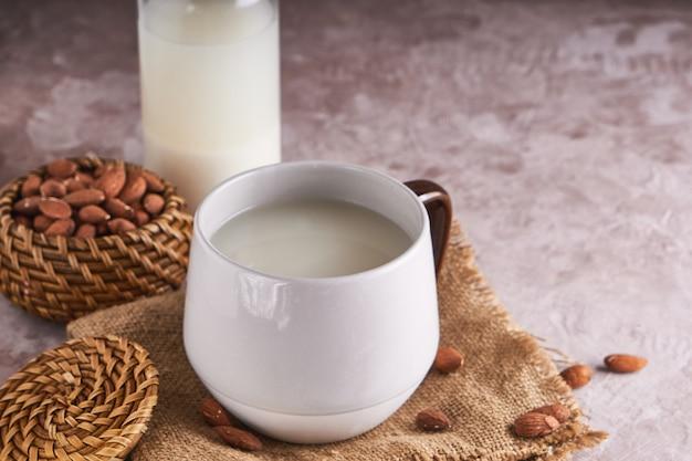 Lait d'amande fait maison dans une tasse et une bouteille, amandes décortiquées sur une surface rustique. aliments et boissons alternatifs.