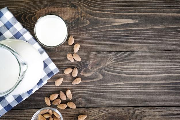 Lait d'amande fraîche en verre et pichet sur fond de table en bois sombre. style rustique.