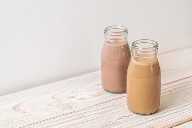 Lait au chocolat et café au lait en bouteille sur table en bois