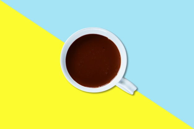 Lait au chocolat chaud sur une tasse en céramique blanche isolée sur fond coloré.