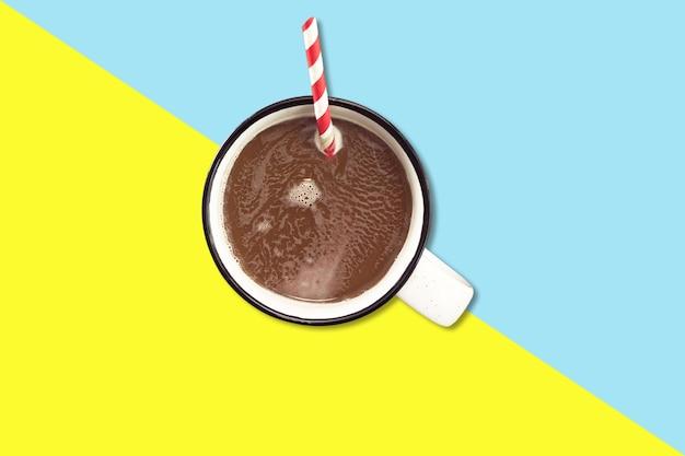 Lait au chocolat chaud sur une tasse en émail blanc avec un rouleau de bâton coloré.