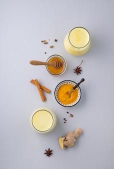 Lait au curcuma, épices et miel sur fond gris