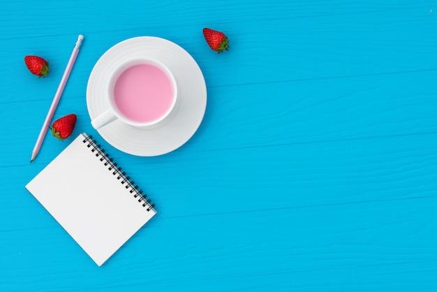 Lait aux fraises de l'espace avec note et crayon sur fond bleu pastel