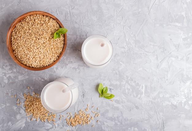 Lait d'avoine biologique non laitier en verre et plaque de bois avec des graines d'avoine sur un béton gris.