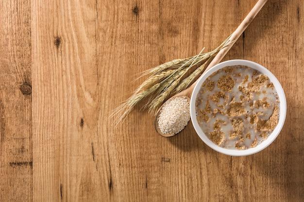 Le lait d'avoine et les céréales dans un bol sur la table en bois copy space