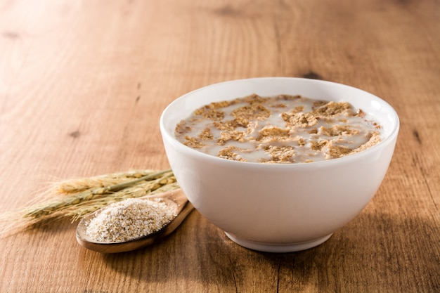 Lait d'avoine et céréales dans un bol sur une table en bois