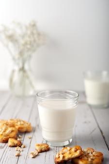 Lait avec des biscuits faits maison fraîchement préparés avec des arachides sur fond clair