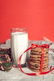 Lait et biscuits sur la surface rouge pour la décoration de noël du père noël nouvel an