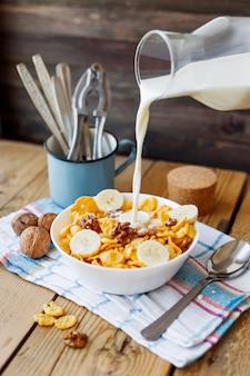 Le lait d'une bouteille coule dans le bol avec de délicieux flocons de maïs aux noix et à la banane. fond en bois rustique avec une serviette à carreaux. collation santé au petit déjeuner croustillant.